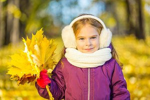 Happy little girl in earflaps with autumn leaves