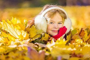 Little girl in earflaps playing with autumn leaves