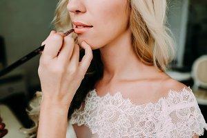Makeup artist makes young beautiful bride bridal makeup. Morning preparation. Close-up hands near face