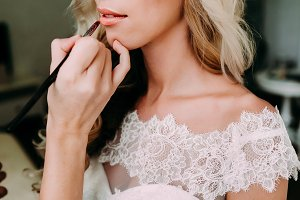 Young beautiful bride applying wedding make-up by make-up artist. Morning preparation. Close-up hands near face