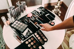 Hands of a makeup artist. Many cosmetics and brushes on a table in the salon. Workplace makeup artist.
