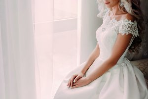 Charming bride blonde with curly hair sits near the window. Wedding. A bride is awaiting her groom.