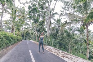 Young woman traveler on the road of jungle, tropical Bali island, Indonesia.