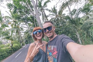 Couple having fun together outdoors. Taking self portrait with camera phone in the jungle of Bali island, Indonesia. Couple selfie.