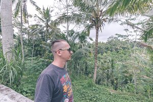 Portrait of a traveler man in sunglasses in the tropical jungle of Bali island, Ubud, Indonesia.