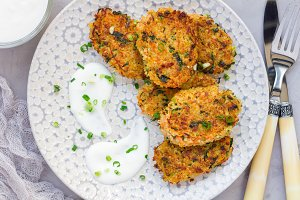 Vegetarian quinoa, carrot, coriander and green onion fritters served with yogurt on plate, horizontal, top view