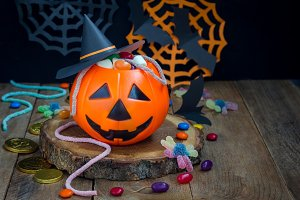 Halloween Jack o Lantern bucket overflowing with candy, spooky Halloween decorations on background, copy space