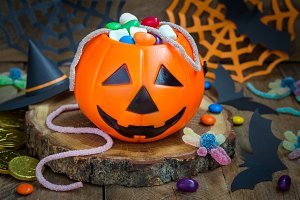 Halloween Jack o Lantern bucket overflowing with candy, spooky decorations on background, horizontal