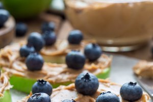 Green apple rounds with peanut butter and and blueberries on wooden table, vertical