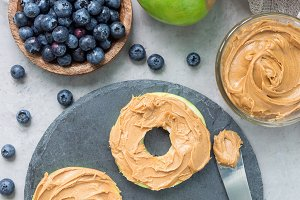 Green apple rounds with peanut butter and and blueberries on slate board, vertical, top view