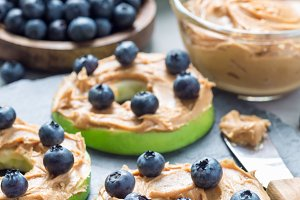 Green apple rounds with peanut butter and and blueberries on slate board, vertical