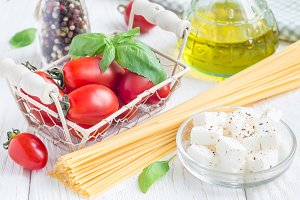 Pasta ingredients. Cherry tomatoes, basil, feta cheese, spaghetti and olive oil on a white wooden background, horizontal