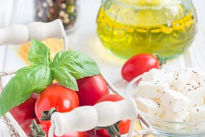 Pasta ingredients. Cherry tomatoes, basil, feta cheese, spaghetti and olive oil on a white wooden background, vertical