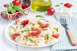 Pasta salad with tie pasta, feta cheese, tomatoes, mustard and basil, horizontal