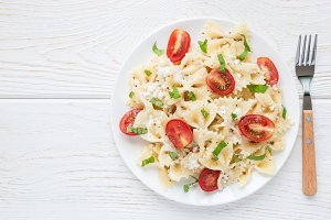 Pasta salad with tie pasta, feta cheese, cherry tomatoes, mustard and basil, top view, copy space