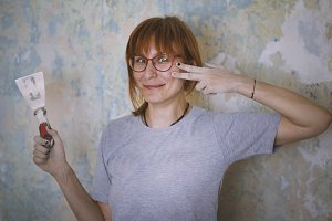Home renovation - red hair woman glues Wallpaper