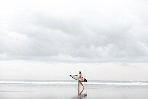 teenage girl in a yellow bikini with her surfboard at a hawaii beach