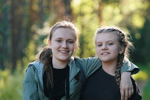Two pretty girls sisters teenagers friends in park - summer outdoor