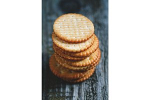 Stack of a of salted crackers on an old wooden table.
