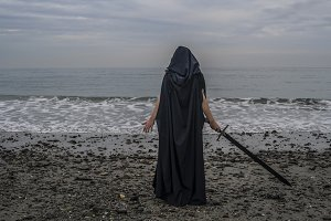 Cloaked warrior on beach with sword