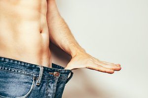Unrecognizable athlet man with a bare torso shows how much he lost weight as a result of a healthy diet pulling his finger to the waist of his trousers