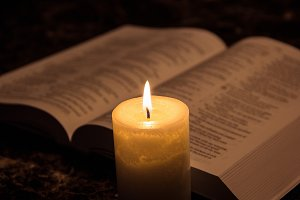 Candle illuminating the bible