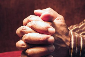 Hands folded Praying on a Holy Bible