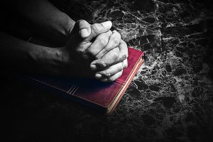 Hands folded in prayer on a Bible