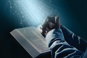 Hands folded in prayer on dark scene
