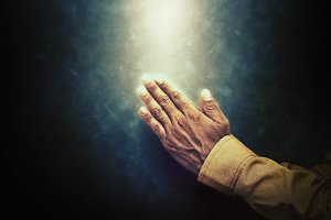 Hands closed in prayer on dark