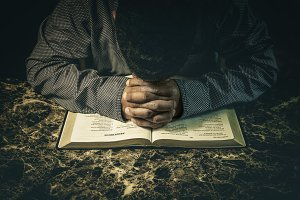 Man praying to God on an open Bible