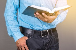 Man Standing Reading The Bible