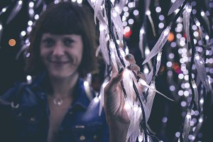 Closely image of young woman among christmas garlands lights. Bali light festival, Indonesia.