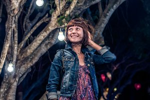 Woman among decorative outdoor string lights hanging on tree in the park at night time. Bali island, Indonesia.