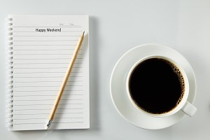 notebook and cup of coffee on wood table