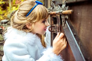 Side view of an little beautiful girl in the scenery looking into the keyhole of the gate