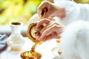 Side view of little beautiful girl's hands in the scenery pouring tea into a cup at the table