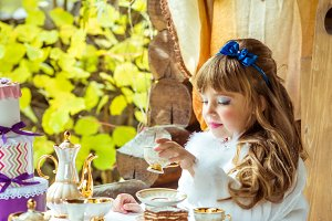 Front view of an little beautiful girl in the scenery holding a cup of tea at the table
