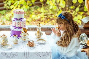 Side view of an little beautiful girl in the scenery drinking a tea at the table in the park