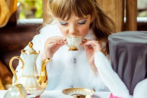 Front view of an little beautiful girl in the scenery drinking a tea at the table in the park