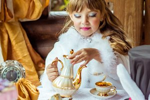 Front view of an little beautiful girl in the scenery pouring tea into a cup at the table