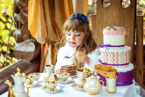 Front view of an little beautiful girl holding a piece of cake on a spoon at the table