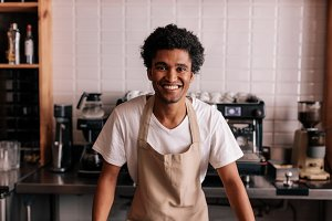 Happy young barista standing