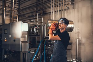 Young man with metal beer barrels