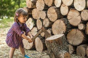A little girl chopping wood