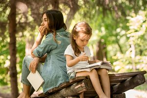 mother and daughter read a book in the park