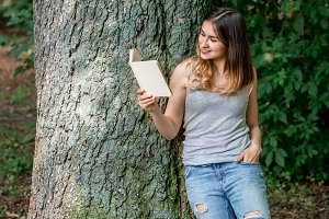 Girl reading a book near a tree