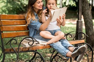 Mom and daughter on a bench reading a book