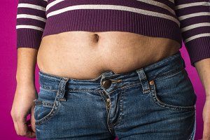 Woman with jeans shows her belly.