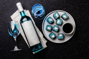 Blue sushi rolls and blue wine chardonnay on black background. Spanish blue wine, trendy drink, Fancy wine, top view. Copy space